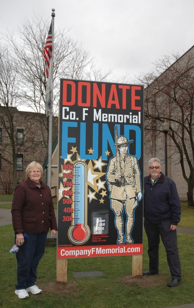 "Company F Committee Members, Cathy Fox and Owen Toale pose with the new ""fundraising gage"" in Rotary Park."