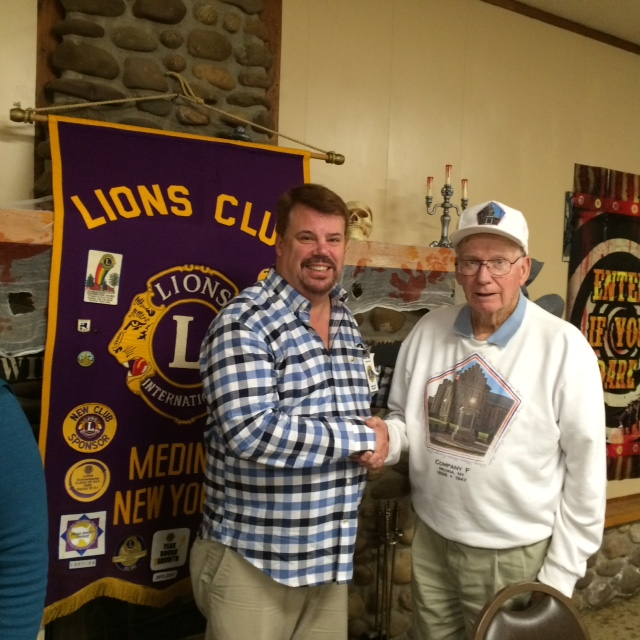 Mark Irwin, Medina Lion's president congratulates Company F Memorial Chairman Bill Menz for the efforts made to honor our veterans.